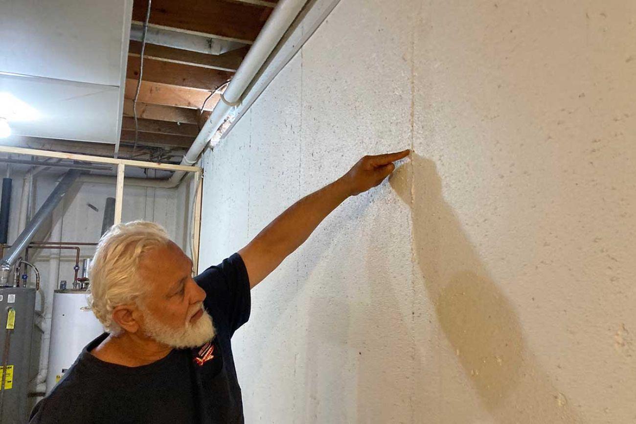 Mohammad Al Hajmoussa inspects wall