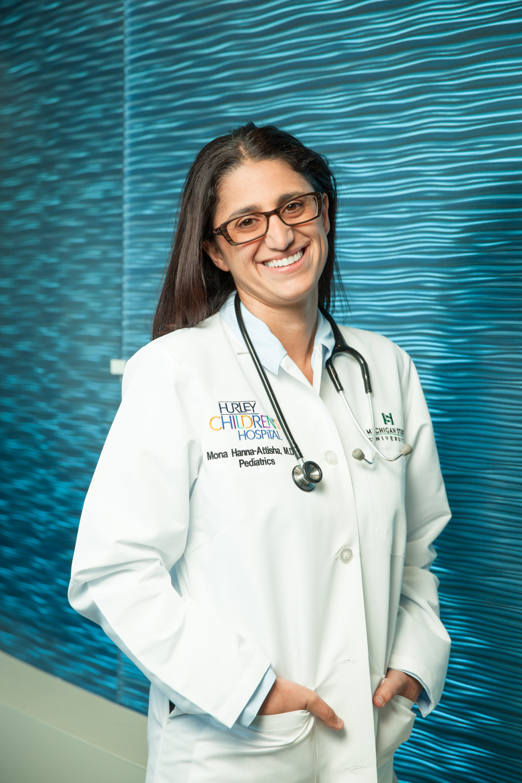 Dr. Mona Hanna-Attisha standing and smiling in front of a blue background
